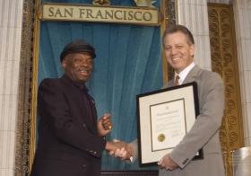 """Onder de gerenommeerde gasten was de burgemeester van San Francisco de heer Willie Brown, die een proclamatie aan de Kerk presenteerde """"voor haar inspanningen om de Bay Area een betere leefomgeving te maken voor al haar bewoners ongeacht, kleur, geloofsovertuiging en of plaats in de samenleving""""."""